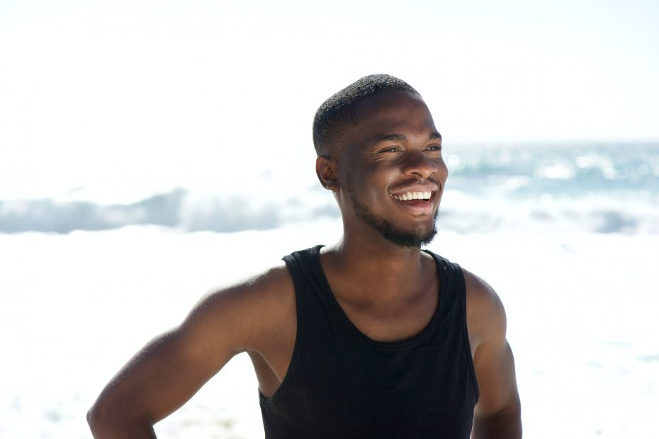 Happy young african american man smiling at the beach